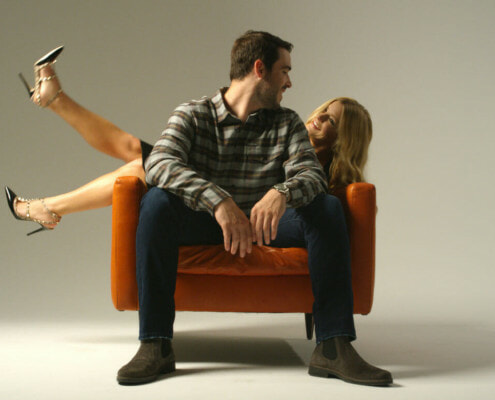 man and woman seated on orange chair looking at each other in studio space