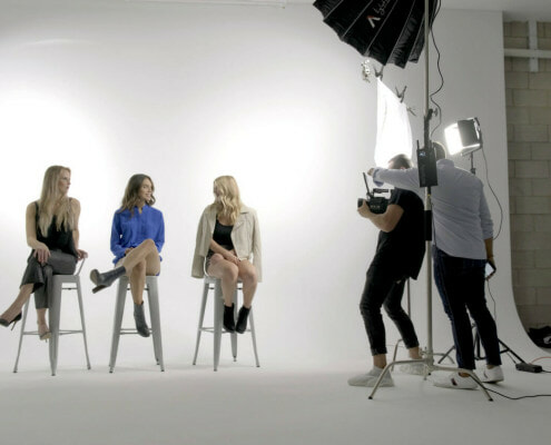 Three models being filmed up against the REV Studio Cyc Wall